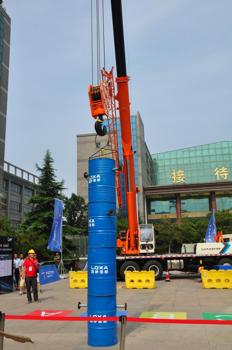 起重机组选手将油桶吊装至指定位置